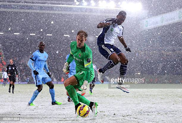 Joe Hart of Manchester City retrieves the ball under pressure from Brown Ideye of West Brom during the Barclays Premier League match between West...
