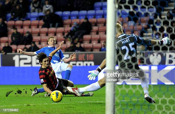 Joe Hart of Manchester City saves the attempt on goal of James McCarthy of Wigan Athletic during the Barclays Premier League match between Wigan...