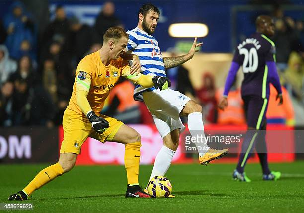 Joe Hart of Manchester City tangles with Charlie Austin of QPR during the Barclays Premier League match between Queens Park Rangers and Manchester...