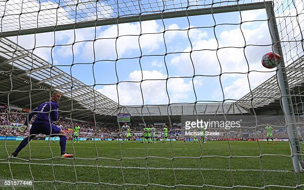Joe Hart of Manchester City watches the ball as Andre Ayew of Swansea City scores his team's first goal from a free kick during the Barclays Premier...