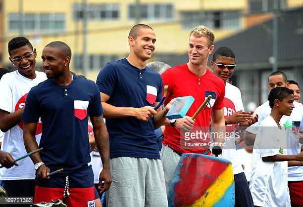 Joe Hartand Jack Rodwell of England share a joke as they play the drums with local children during a visit to a Sport Relief project on May 31 2013...