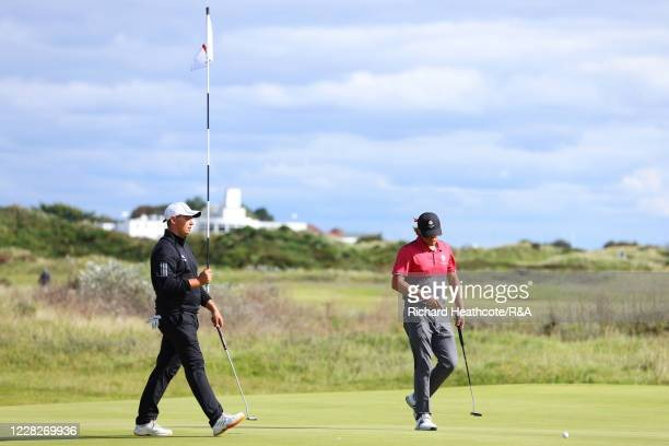 Joe Harvey of England holds the pin on the 11th hole in the afternoon round during the Final on Day Six of the Amateur Championship at Royal Birkdale...