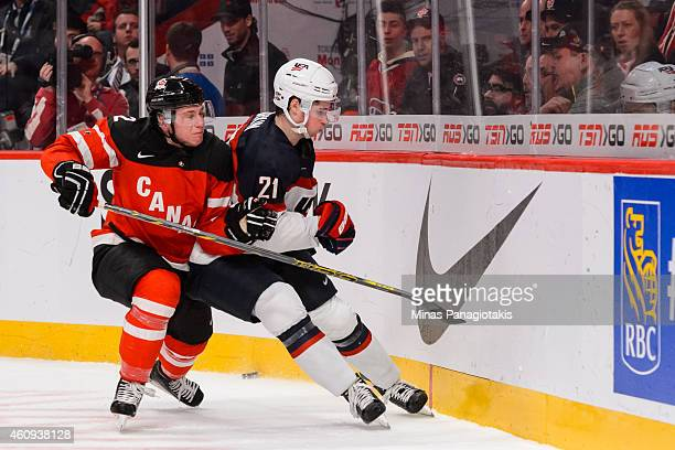 Joe Hicketts of Team Canada pushes Dylan Larkin of Team United States into the boards in a preliminary round game during the 2015 IIHF World Junior...