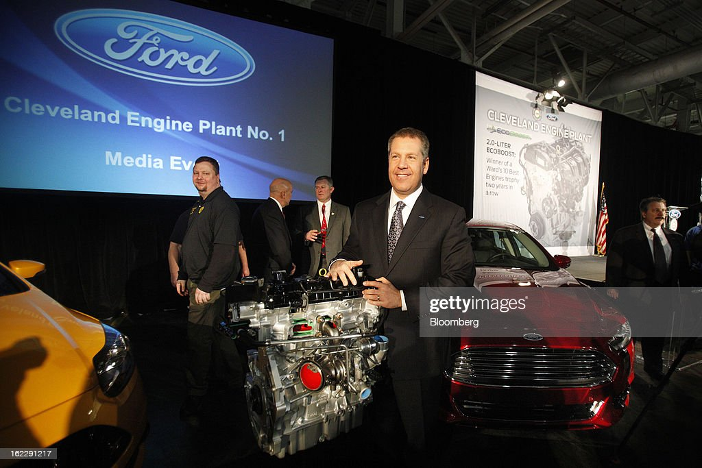 Joe Hinrichs, president of the Americas for Ford Motor Co., stands for a photograph next to a 2.0 liter ecoboost engine during an event at the company's Cleveland Engine Plant in Brook Park, Ohio, U.S., on Thursday, Feb. 21, 2013. Ford Motor Co. said it will invest $200 million to make four-cylinder engines at the plant starting in late 2014 as the second-largest U.S. automaker equips an increasing number of models with smaller, more fuel-efficient powertrains. Photographer: David Maxwell/Bloomberg via Getty Images