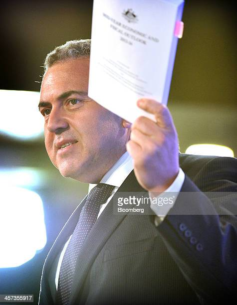 Joe Hockey Australia's treasurer holds a copy of the government's midyear economic and fiscal outlook during a presentation in Canberra Australia on...