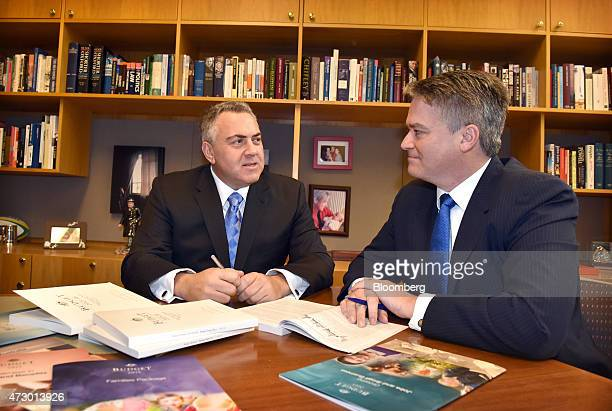 Joe Hockey Australia's treasurer left and Mathias Cormann Australia's finance minister pose for photographs with copies of the federal budget at...
