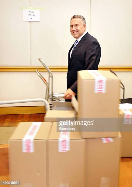 Joe Hockey Australia's treasurer smiles for a photograph as he walks past boxes of unopened treasury documents while in the budget lockup at...
