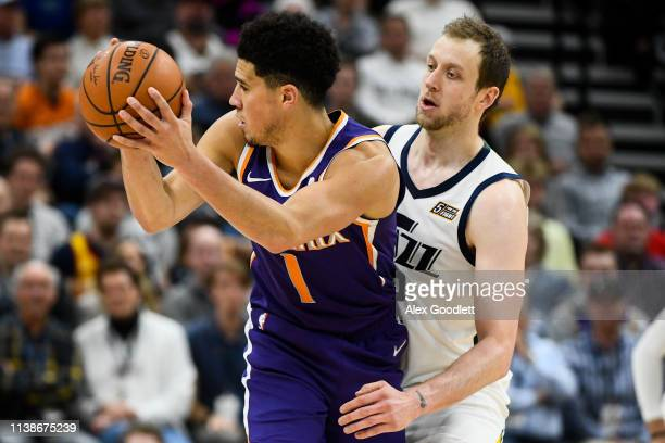 Joe Ingles of the Utah Jazz guards Devin Booker of the Phoenix Suns during a game at Vivint Smart Home Arena on March 25, 2019 in Salt Lake City,...
