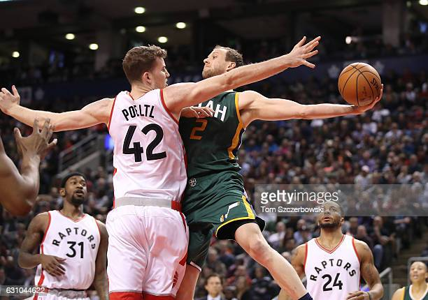 Joe Ingles of the Utah Jazz passes the ball under the basket as Jakob Poeltl of the Toronto Raptors guards him during NBA game action at Air Canada...