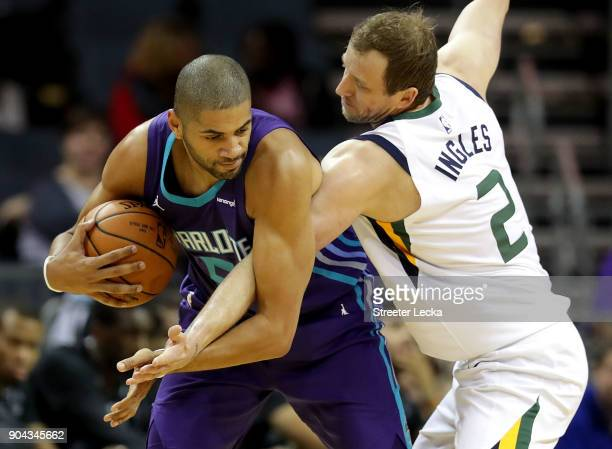 Joe Ingles of the Utah Jazz tries to stop Nicolas Batum of the Charlotte Hornets during their game at Spectrum Center on January 12 2018 in Charlotte...