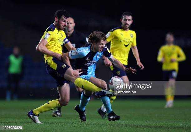 Joe Ironside of Cambridge United is tackled by Elliott Moore of Oxford United during the Papa John's Trophy match between Oxford United and Cambridge...