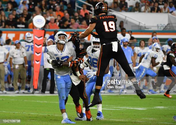Joe Jackson and Scott Patchan of the Miami Hurricanes sack Chazz Surratt of the North Carolina Tar Heels in the second quarter during the game...