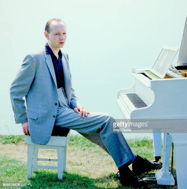 Joe Jackson posing with a white grand piano on the cliff above Folkestone Harbour on the 4th June 1982 during the making of a promotional film for...