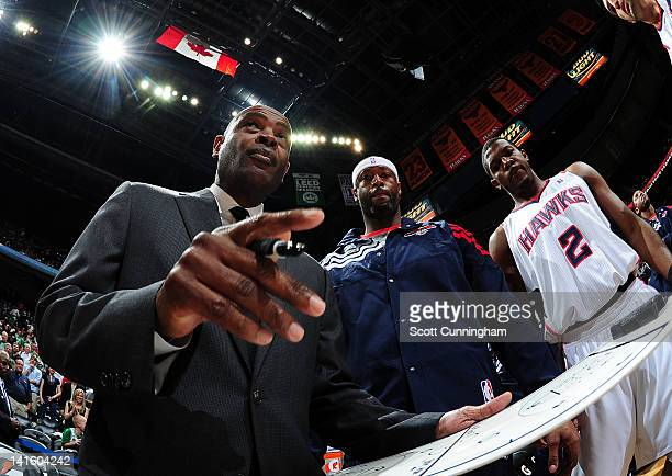 Joe Johnson and Erick Dampier of the Atlanta Hawks listen to head coach Larry Drew during a game against the Boston Celtics on March 19 2012 at...