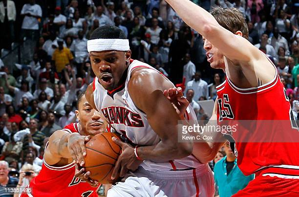 Joe Johnson of the Atlanta Hawks drives between Derrick Rose and Kyle Korver of the Chicago Bulls in Game Four of the Eastern Conference Semifinals...
