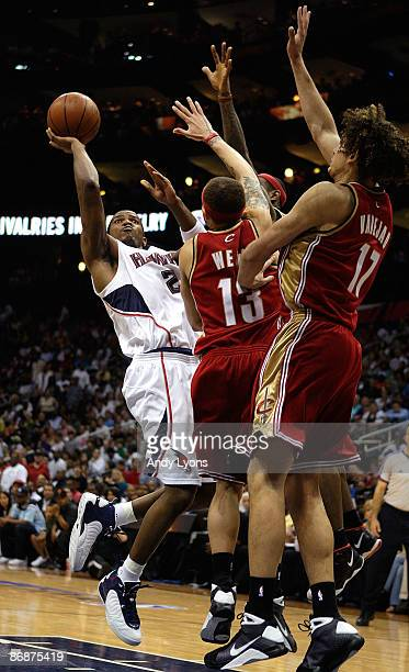 Joe Johnson of the Atlanta Hawks shoots against Delonte West and Anderson Varejao of the Cleveland Cavaliers in Game Three of the Eastern Conference...