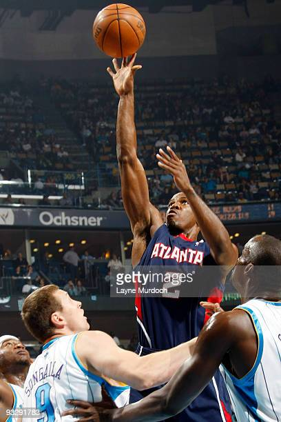 Joe Johnson of the Atlanta Hawks shoots over Devin Brown Darius Songaila and Emeka Okafor of the New Orleans Hornets on November 21 2009 at the New...