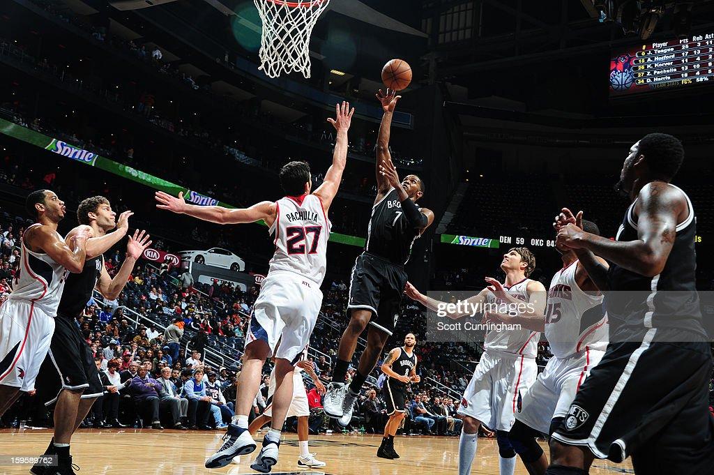 Joe Johnson #7 of the Brooklyn Nets shoots against Zaza Pachulia #27 of the Atlanta Hawks on January 16, 2013 at Philips Arena in Atlanta, Georgia.