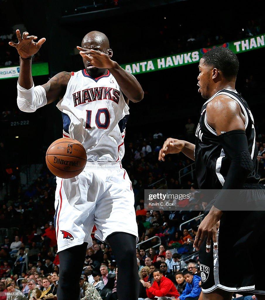 Joe Johnson #7 of the Brooklyn Nets strips the ball from Johan Petro #10 of the Atlanta Hawks at Philips Arena on March 9, 2013 in Atlanta, Georgia.