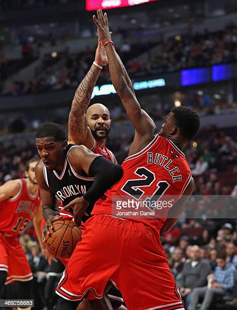 Joe Johnson of the Brooklyn Nets tries to get between Carlos Boozer and Jimmy Butler of the Chicago Bulls at the United Center on February 13 2014 in...