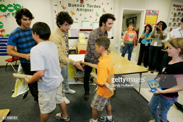 Joe Jonas Nick Jonas and Kevin Jonas of The Jonas Brothers greet students as part of the Topps Baby Bottle Pop School Concert Invasion for students...
