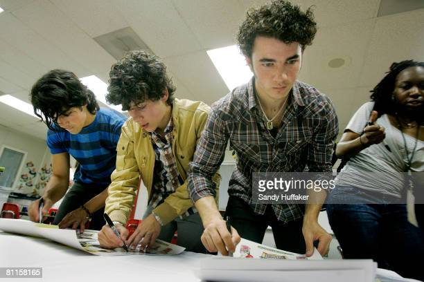 Joe Jonas Nick Jonas and Kevin Jonas of The Jonas Brothers sign autographs as part of the Topps Baby Bottle Pop School Concert Invasion for students...