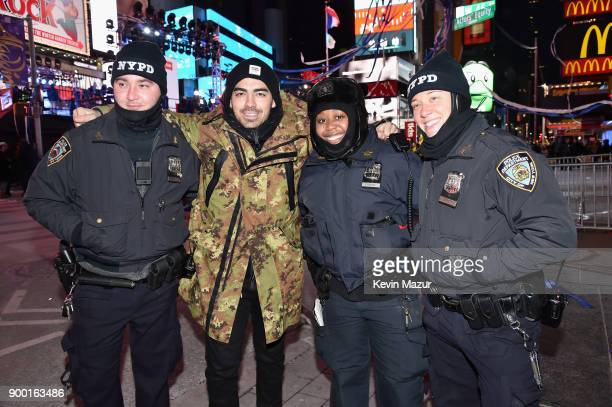 Joe Jonas poses with NYPD officers at the Dick Clark's New Year's Rockin' Eve with Ryan Seacrest 2018 on December 31 2017 in New York City