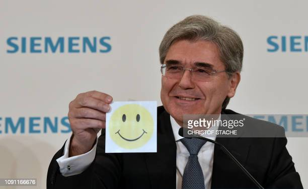 Joe Kaeser German industrial giant Siemens shows a leaflet with a Smiley drawing on it during a press conference ahead of the company's annual...
