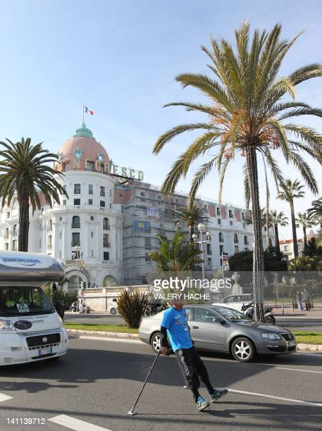 Joe Kals a paraplegic for thirty years walks using crutches in the southeastern French city of Nice on March 11 2012 Kals who has already traveled...