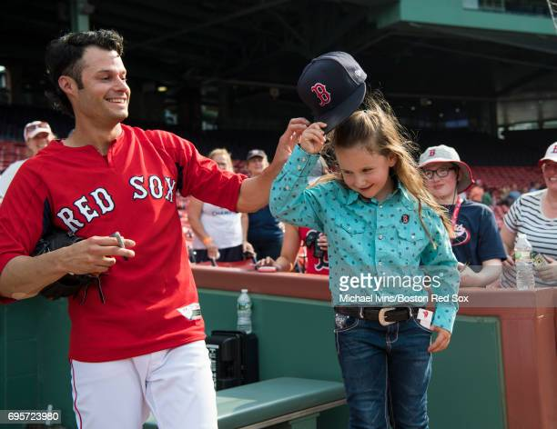 Joe Kelly of the Boston Red Sox gives his hat to Macey Hensley, a frequent guest on the Ellen DeGeneres show, at Fenway Park on June 13, 2017 in...