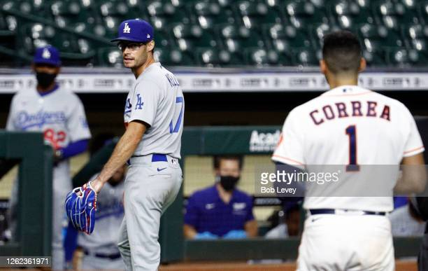 Joe Kelly of the Los Angeles Dodgers has words with Carlos Correa of the Houston Astros as he walks towards the dugout at Minute Maid Park on July 28...