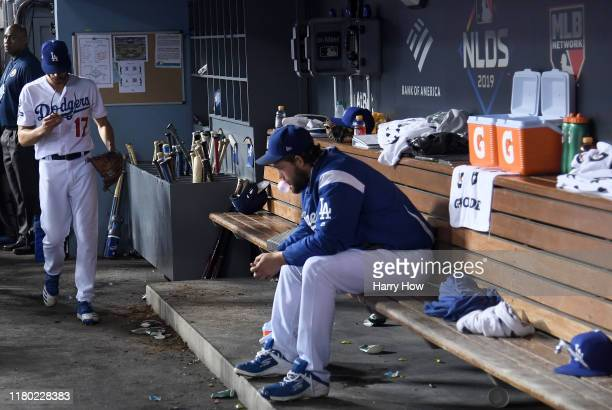Joe Kelly of the Los Angeles Dodgers walks in the dugout after being pulled as Clayton Kershaw sits dejected on the bench in the tenth inning of game...