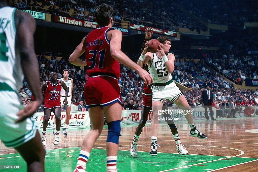 Joe Kleine #53 of the Boston Celtics rebounds against the Washington Bullets during a game played in 1990 at the Boston Garden in Boston, Massachusetts.