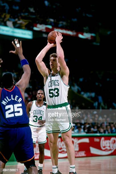 Joe Kleine of the Boston Celtics shoots against Oliver Miller of the Phoenix Suns during a game played at the Boston Garden in Boston Massachusetts...
