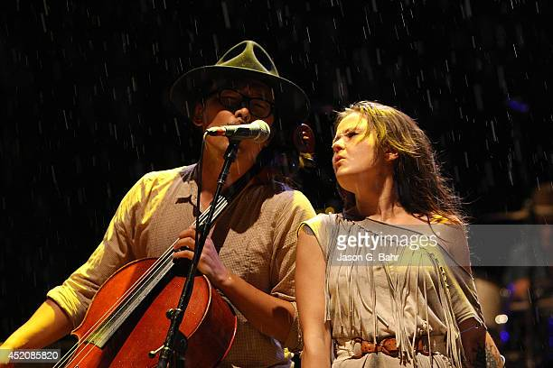 Joe Kwon and Tania Elizabeth of The Avett Brothers perform through the rain at Red Rocks Amphitheatre on July 12 2014 in Morrison Colorado