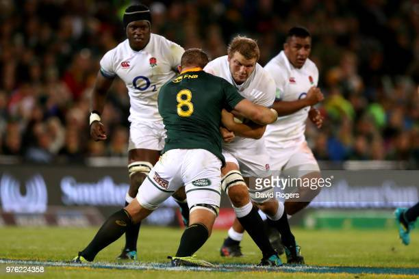 Joe Launchbury of England is held in the tackle by South Africa's Duane Vermulen during the second test match between South Africa and England on...