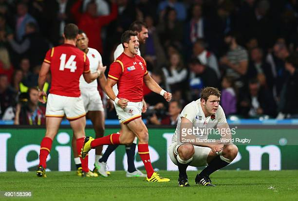 Joe Launchbury of England sits dejected on his haunches as the Wales team celebrate victory during the 2015 Rugby World Cup Pool A match between...