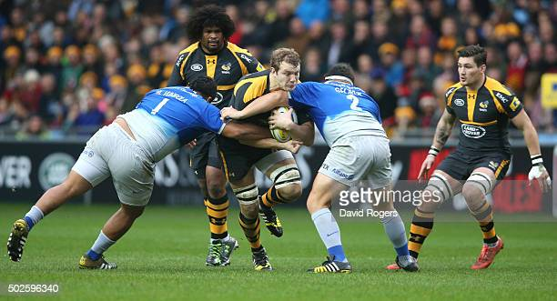 Joe Launchbury of Wasps is tackled by Mako Vunipola and Jamie George during the Aviva Premiership match between Wasps and Saracens at The Ricoh Arena...