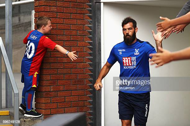 Joe Ledley of Crystal Palace high fives fans as he enters the ptich to warm up during the Premier League match between Crystal Palace and AFC...