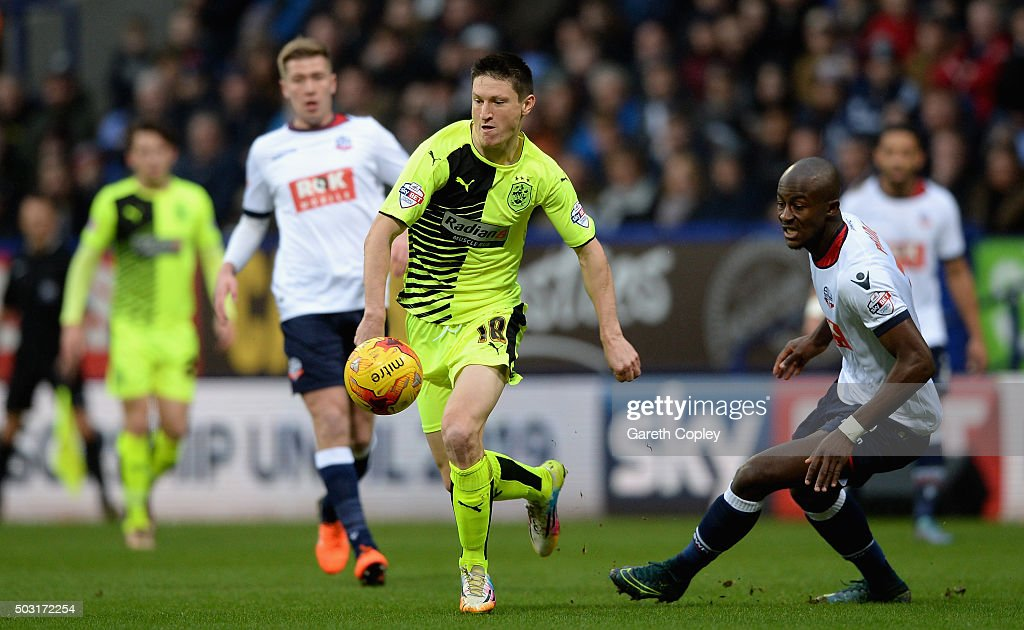 Joe Lolley of Huddersfield Town gets padst Prince-Desir Gouano of Bolton during the Sky Bet Championship match between Bolton Wanderers and Huddersfield Town at the Macron Stadium on January 2, 2016 in Bolton, United Kingdom.