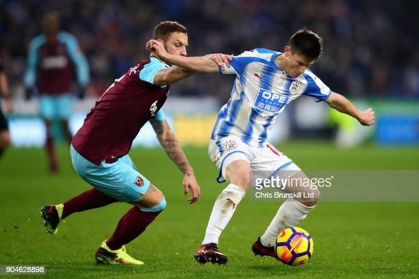 Joe Lolley of Huddersfield Town is challenged by Marko Arnautovic of West Ham United during the Premier League match between Huddersfield Town and...