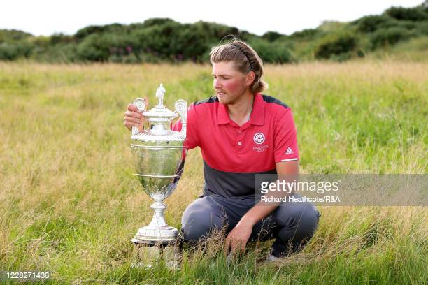 Joe Long of England looks at the trophy following his 4&3 victory during the Final on Day Six of the Amateur Championship at Royal Birkdale on August...