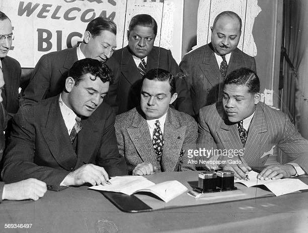Joe Louis and his managers sealing the works for the heavyweight championship bought in June in Chicago with white titleholder Jim Braddock 1937