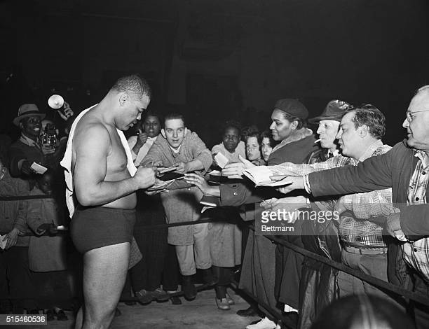 Joe Louis is shown as autograph hunters converged on him after he defeated Don Cowboy Rocky Lee in his debut tonight as a pro wrestler