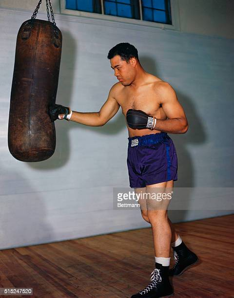 Joe Louis the heavyweight champion of the 1930's and 1940's, works out by punching a heavy bag.