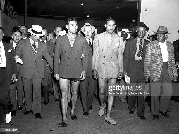Joe Louis vs Max Schmeling II Max Schmeling and Joe Louis look as though they've been sold some no pants suits as they parade to the scales at big...
