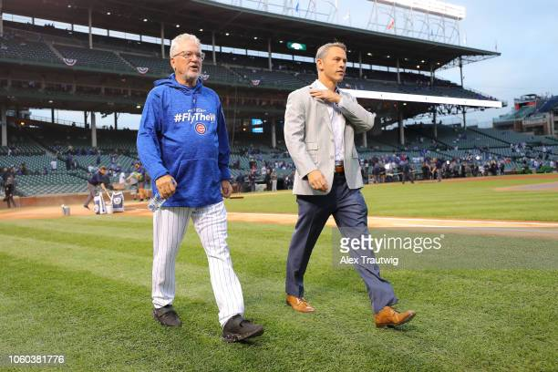 Joe Maddon of the Chicago Cubs and General Manager Jed Hoyer look on before the National League Wild Card game against the Colorado Rockies at...