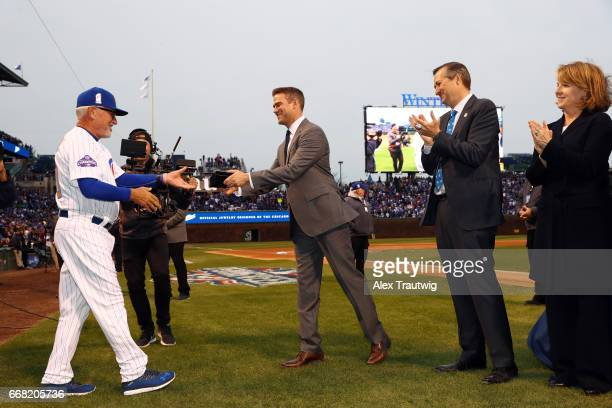 Joe Maddon of the Chicago Cubs is greeted by President of Baseball Operations Theo Epstein and owner Tom Ricketts during the World Series ring...