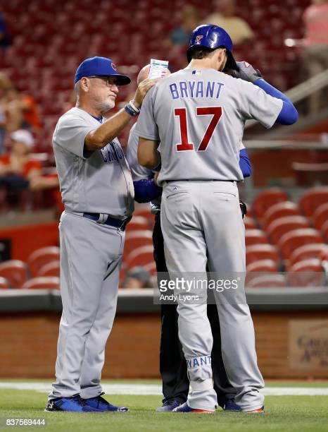 Joe Maddon the manager of the Chicago Cubs checks on Kris Bryant after Bryant was hit by a pitch in the 9th inning against the Cincinnati Reds at...