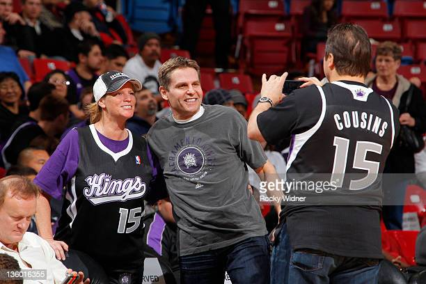 Joe Maloof , an owner of the Sacramento Kings, poses for a photo with a fan as his brother and co-owner Gavin Maloof takes a picture during an open...